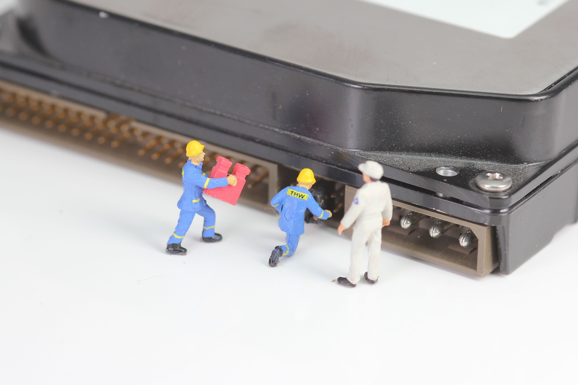 Miniature clay workmen adding and removing pieces from the back of a computer
